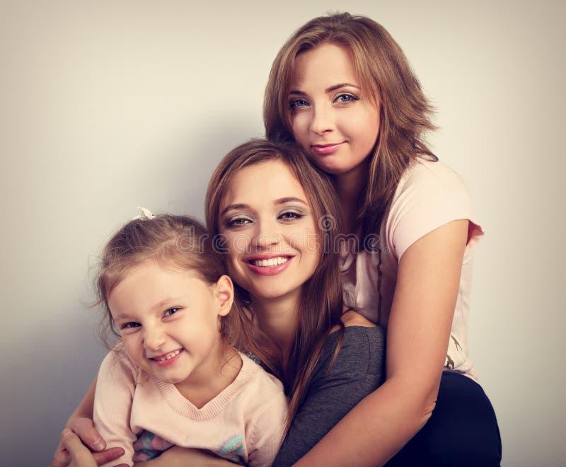 两名年轻美丽的微笑的妇女和愉快joying哄骗女孩hugg 免版税库存照片