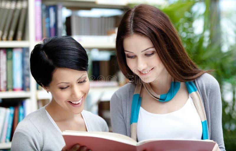 两名兴高采烈的学生读在图书馆 库存图片