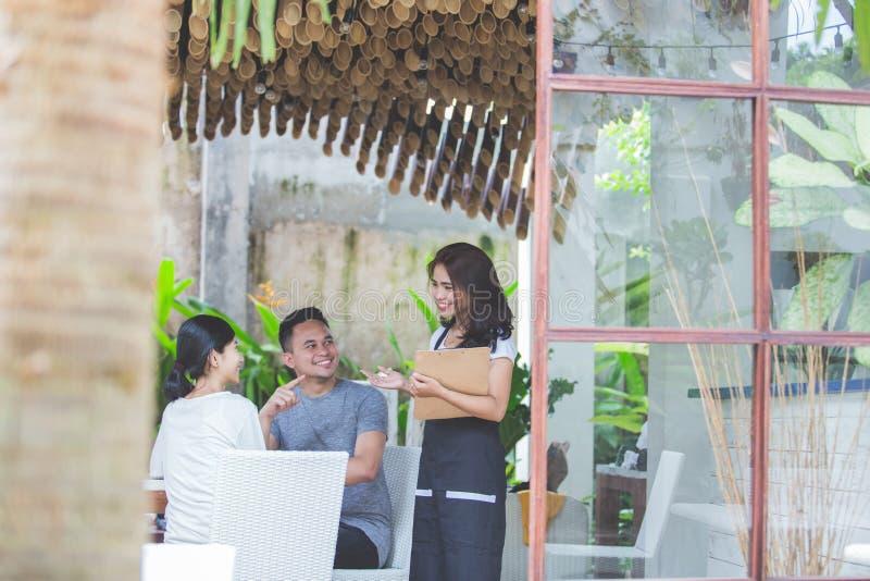 两咖啡馆的朋友谈话与点的女服务员一些食物 库存图片
