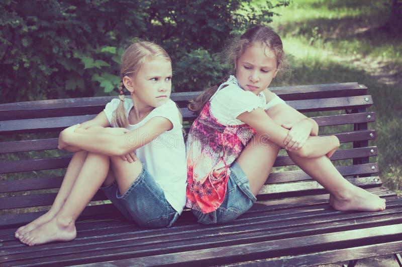 两哀伤的姐妹坐长凳在公园 库存照片