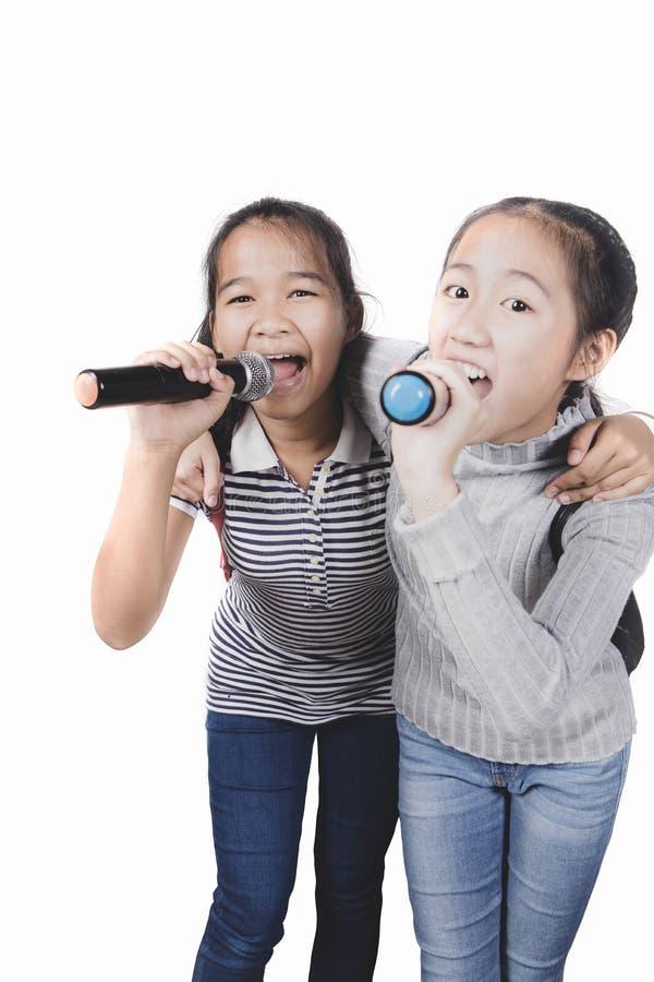 两唱歌有话筒被隔绝的白色背景的快乐的亚裔少年 图库摄影