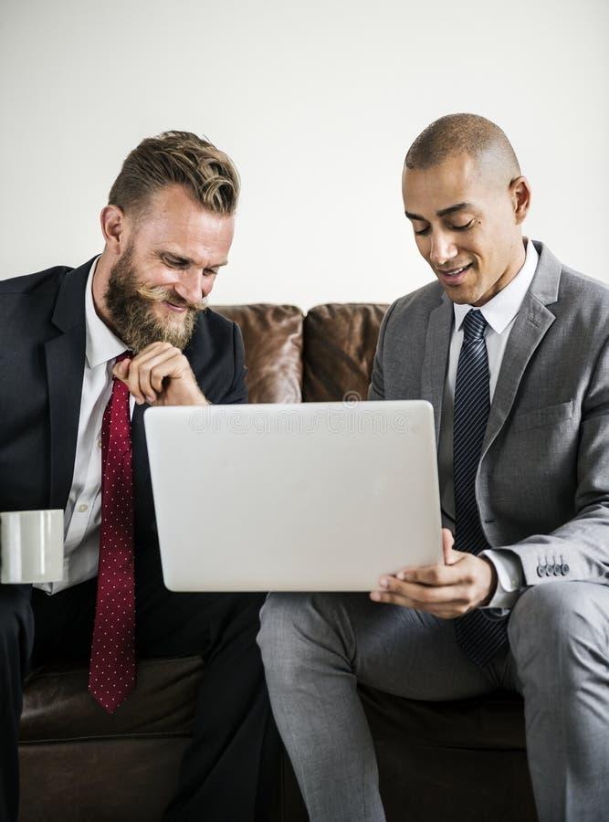 两商人坐研究膝上型计算机的长沙发 免版税图库摄影