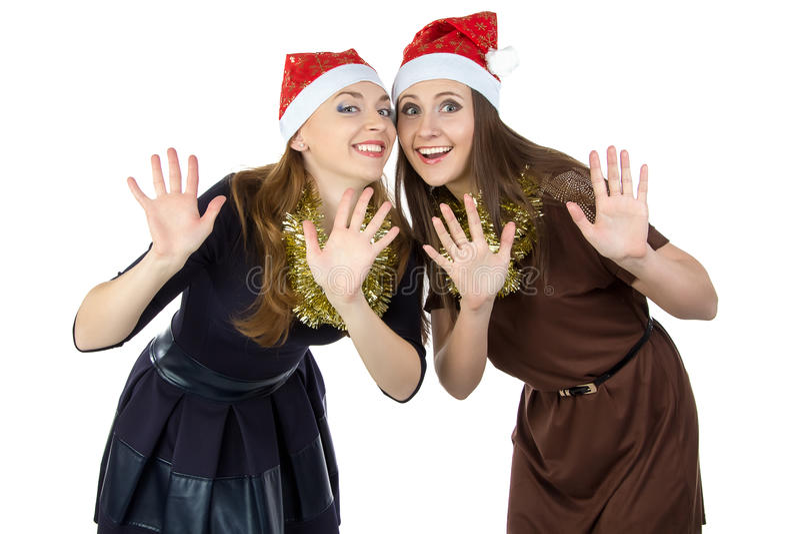 两圣诞节帽子的愉快的少妇的图象 免版税库存照片