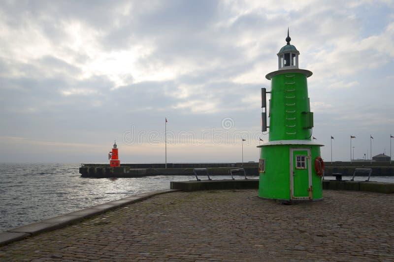两在入口的老灯塔对赫尔新哥,多云天口岸镇  丹麦 免版税图库摄影