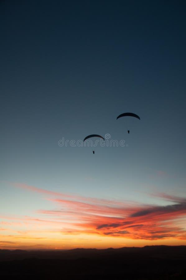 两在日落的滑翔伞剪影  免版税库存照片