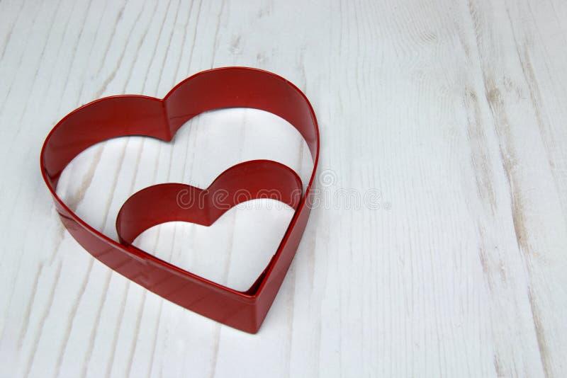 两在木白色后面的红色心形的曲奇饼切削刀 库存图片