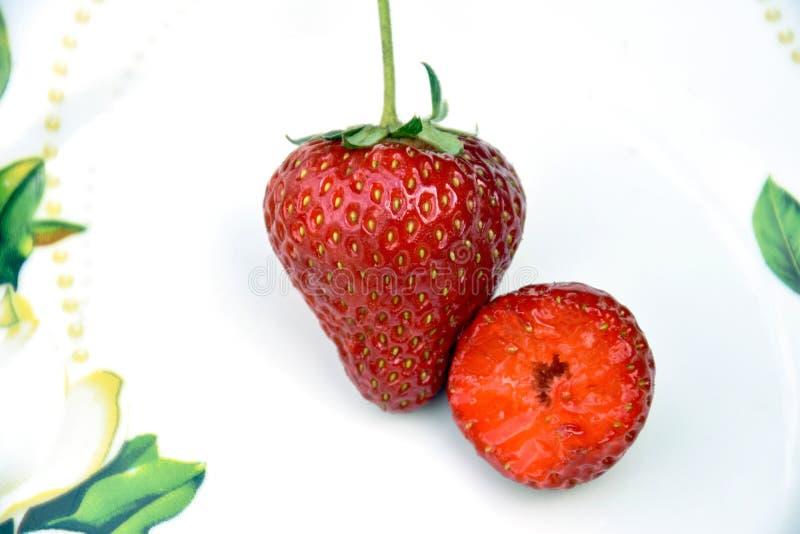 两在板材的成熟红色Strawberrys 整个和半 r 库存图片