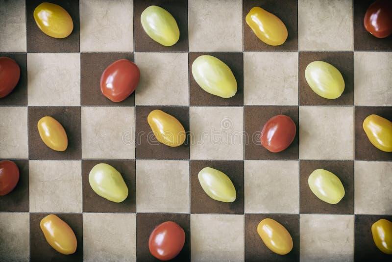 两在棋枰的多彩多姿的成熟西红柿,顶视图 背景几何老装饰品纸张葡萄酒 健康概念的食物 库存图片