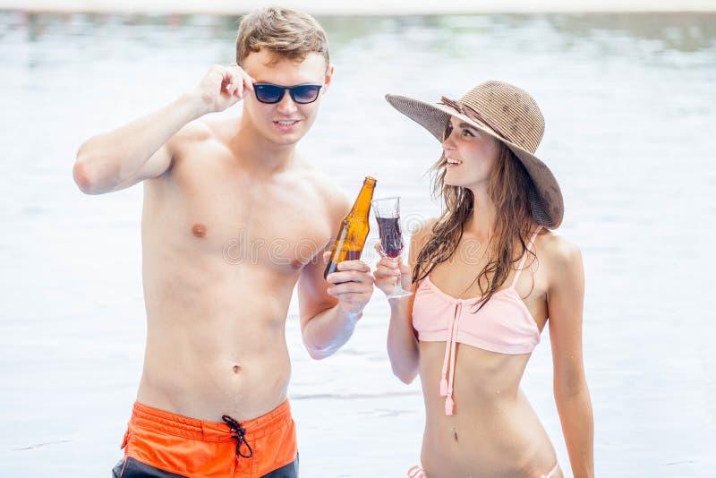 两在水池的年轻制造的党和与i的饮用的饮料 免版税库存图片