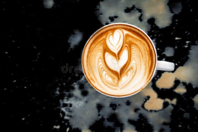 两在白色杯子的心脏拿铁艺术  在黑色的肮脏的溢出咖啡 免版税库存照片