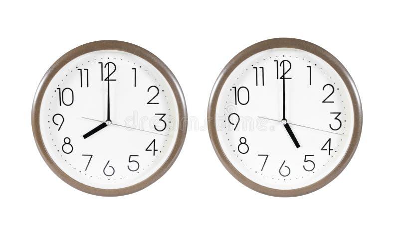两在白色背景隔绝的棕色壁钟 在八的被隔绝的壁钟和5点 被隔绝的壁钟 免版税库存图片