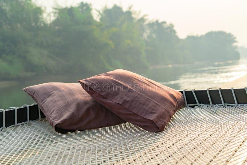 两在网的枕头在早晨日出的漂流的村庄大阳台 免版税库存图片