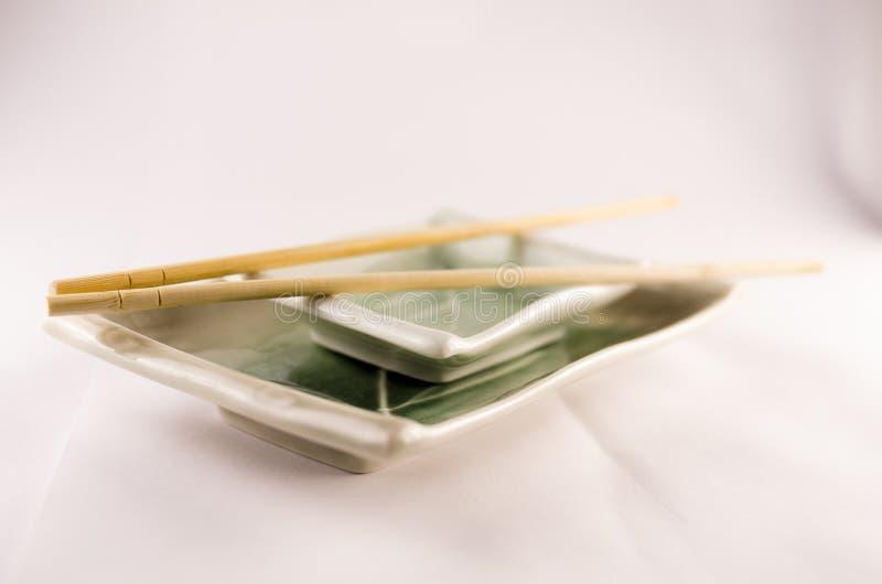 两块寿司板材用在白色背景的棍子 免版税库存图片