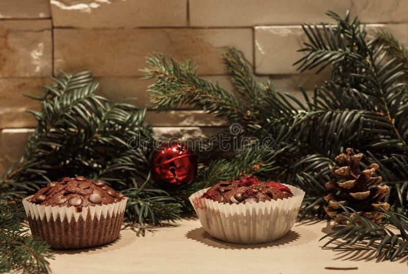 两块巧克力杯形蛋糕和红色响铃 免版税图库摄影