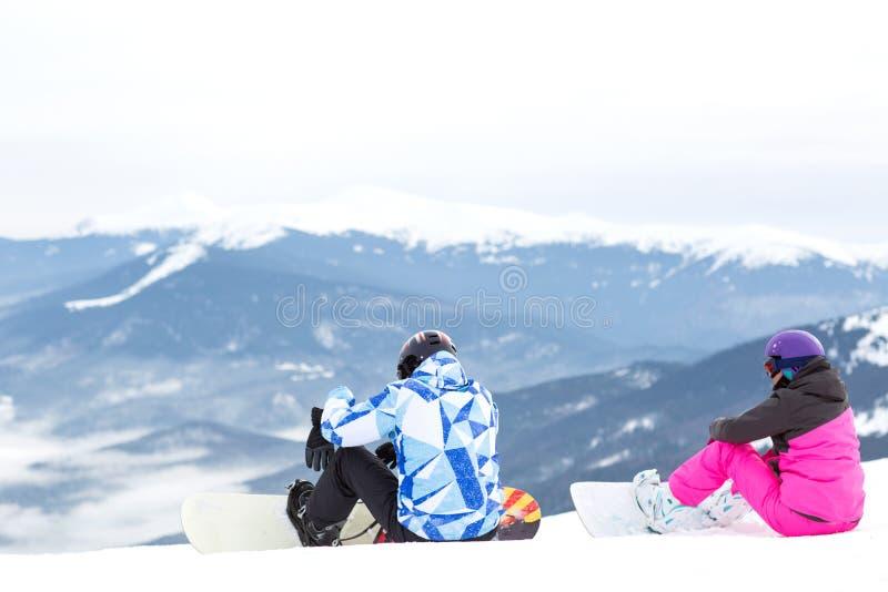 两块挡雪板坐一个高山倾斜 免版税库存照片