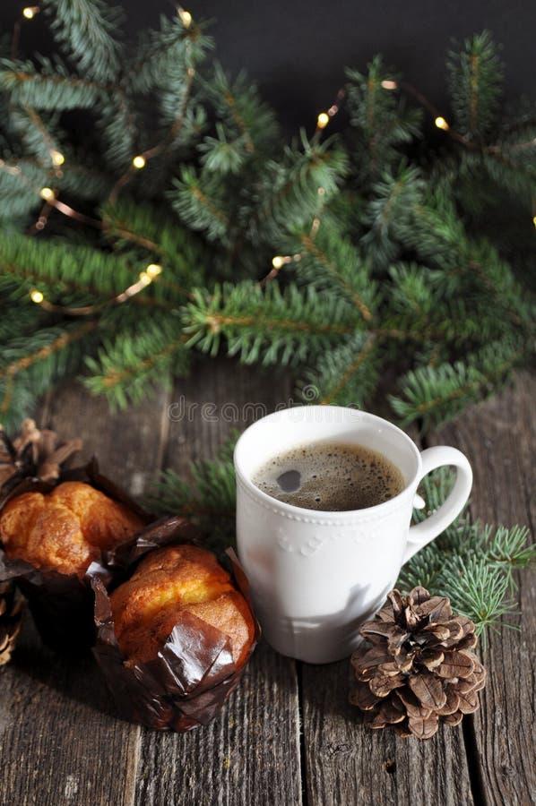 两块杯形蛋糕和一杯圣诞节早餐在一张木桌上的热的咖啡,在冷杉分支背景与光的 库存图片