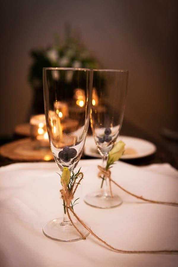 两块空的香槟玻璃包含蓝莓,用黄色花装饰并且与a一起被栓 库存图片