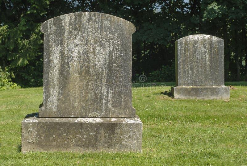 两块老墓碑在一座公墓在一个晴天 免版税库存照片