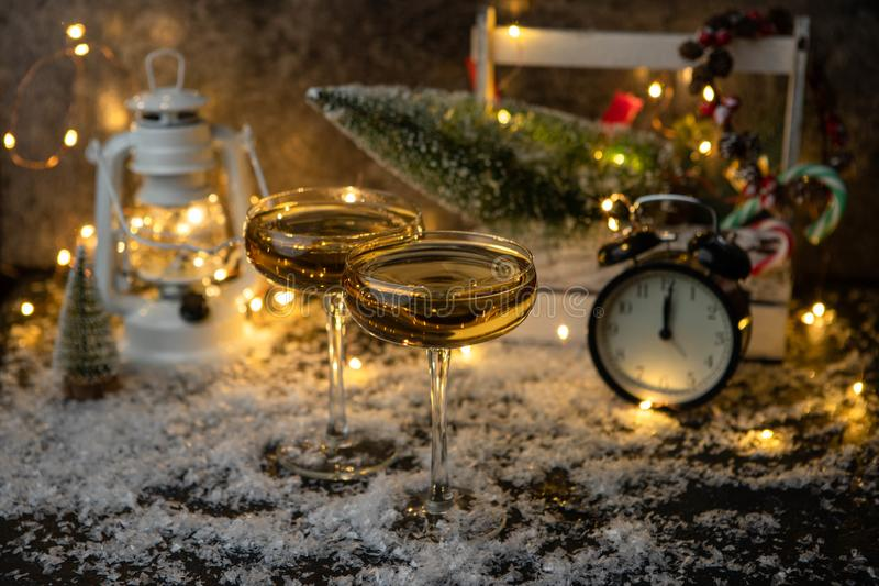 两块香槟玻璃的图象在被弄脏的背景的与圣诞树,灯笼,时钟 免版税库存图片