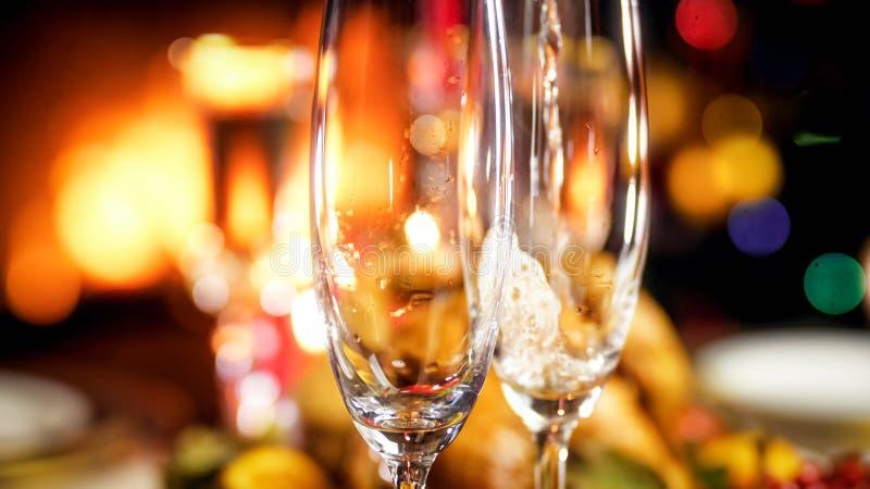 两块香槟玻璃的特写镜头图象在桌上的在灼烧的壁炉旁边 免版税库存照片