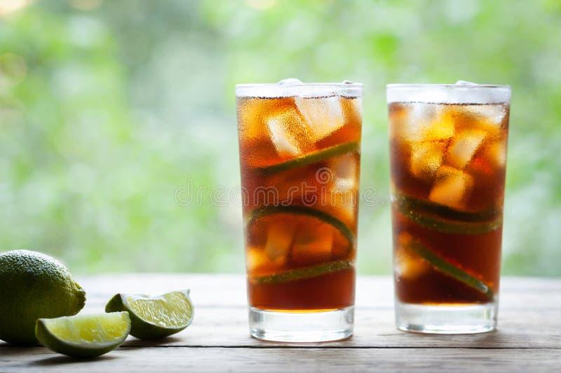 两块玻璃与石灰、冰、薄菏和兰姆酒在木桌上与草帽和看法的古巴Libre鸡尾酒对大阳台 库存照片