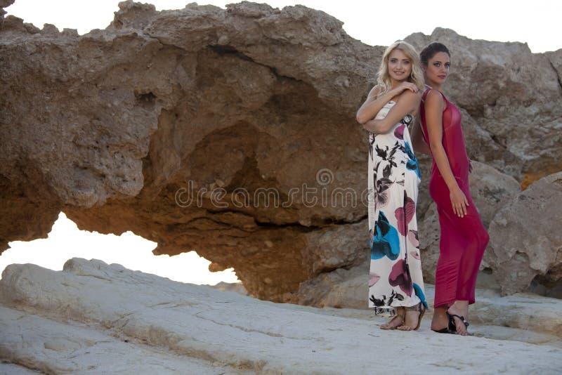 两夏天礼服的妇女在岩石 免版税库存照片