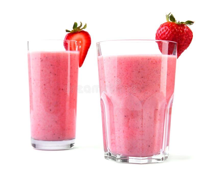 两大和与由水多和新鲜的红色草莓和牛奶做的寒冷和桃红色饮料的不同的玻璃 免版税库存照片