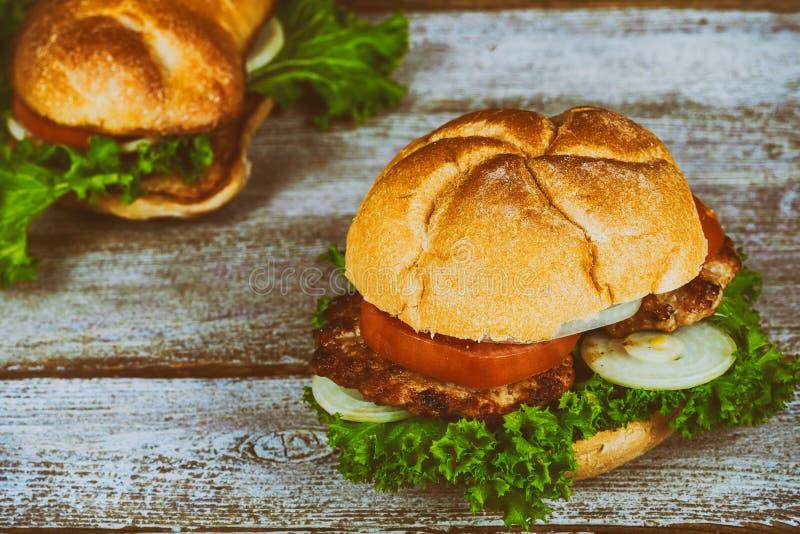 两大自创可口cheesburger,用葱,烤了烟肉,新鲜的蕃茄,新鲜的鲜美汉堡木桌 免版税图库摄影