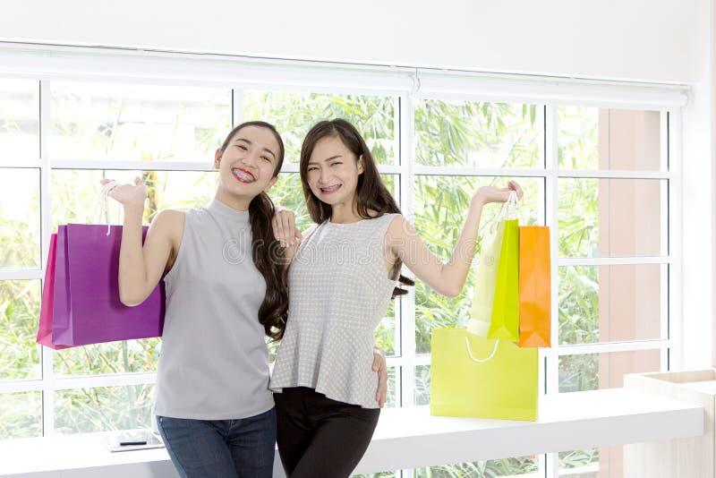 两夫人满意对购物袋在手边 购物妇女smili 库存图片