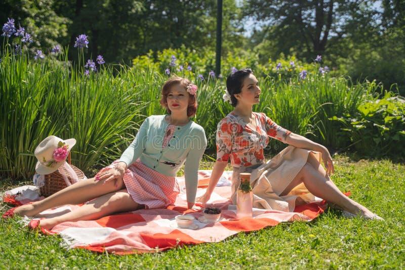 两夫人的俏丽的别针有好的野餐在城市公园在一好日子一起 女朋友享受热的夏天天气 ?? 库存照片