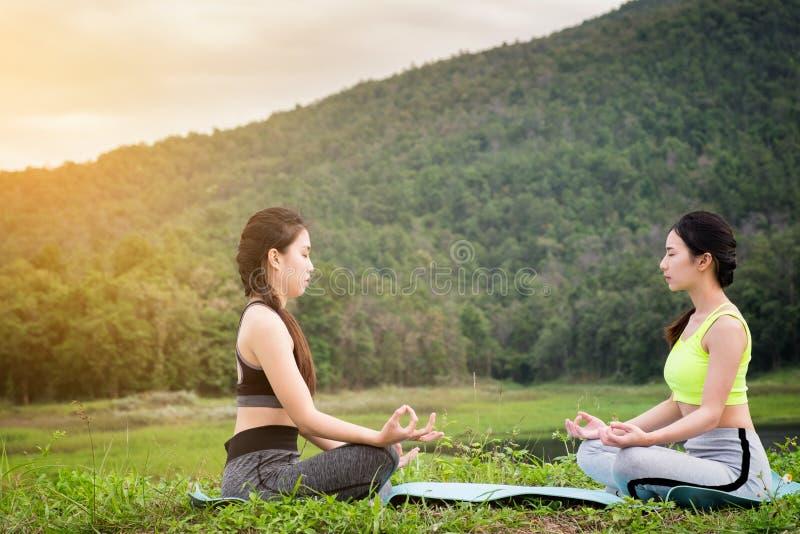 两女子瑜伽在公园,健康妇女,瑜伽妇女 概念  免版税库存图片