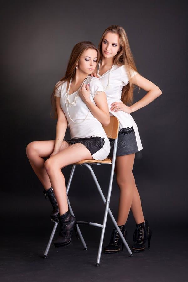 两女孩孪生,隔绝在黑色 免版税库存照片