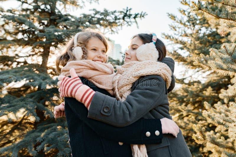 两女孩室外冬天画象微笑和获得乐趣在圣诞树附近,金黄小时 库存照片