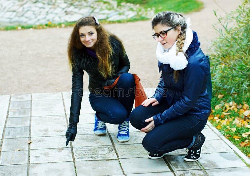 两女孩步行在秋天公园 免版税库存照片