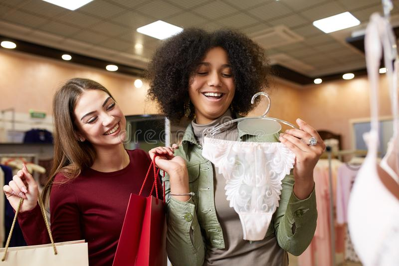 两女用贴身内衣裤的愉快的别致的年轻混合的族种妇女购物在与一举行的内裤的衣物精品店作为他们 库存照片