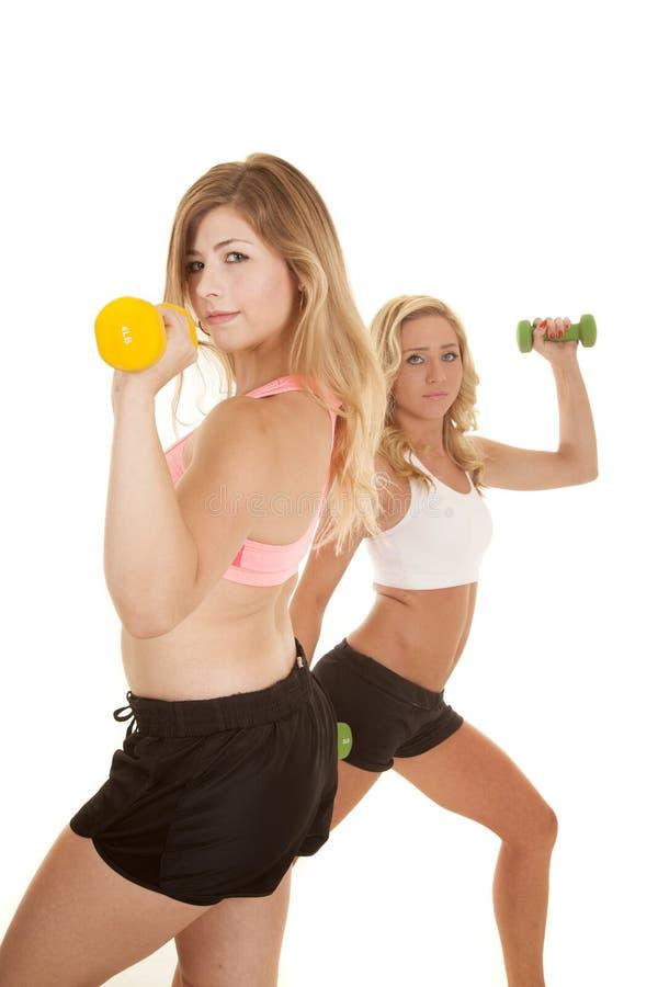 两妇女锻炼体育胸罩前面黄色重量 免版税库存图片
