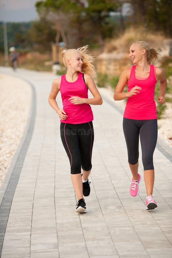两妇女athlets跑在海滩的-清早夏天w 库存图片