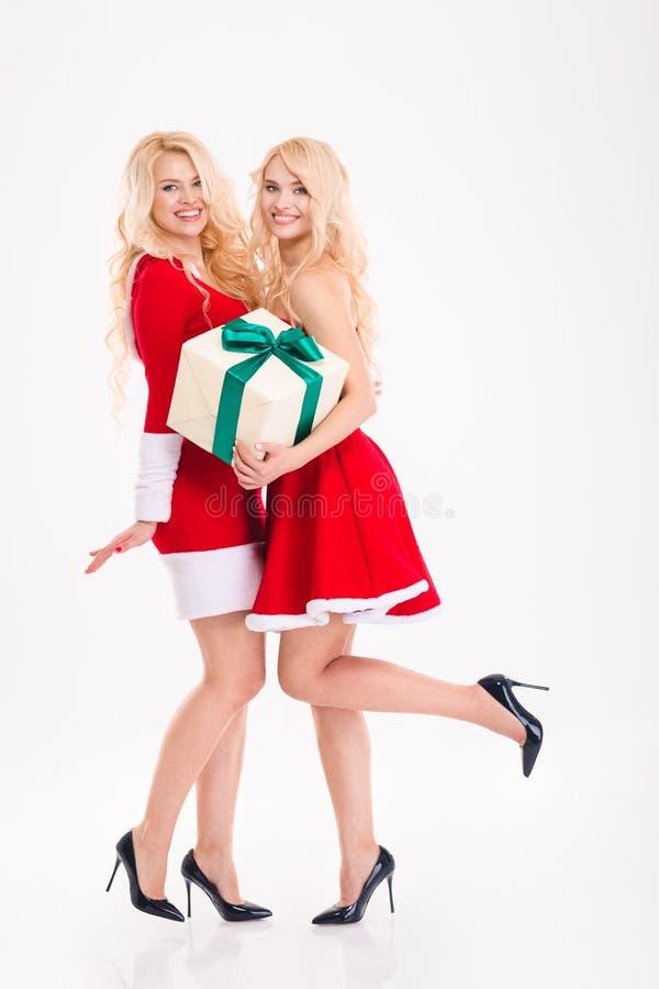 两姐妹孪生在圣诞老人穿戴拿着一个礼物 库存照片