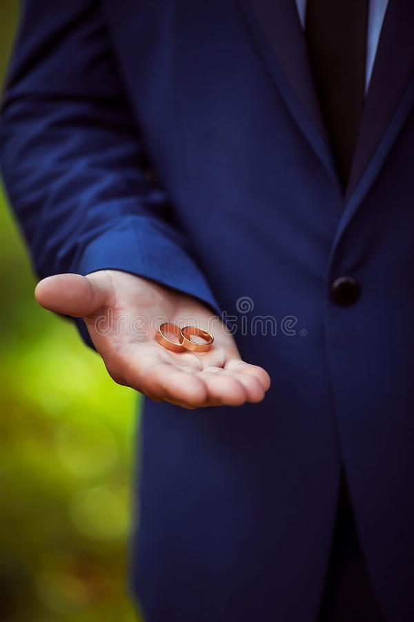 两婚姻的金结婚戒指在人特写镜头的手上,新郎,婚姻的辅助部件 库存图片