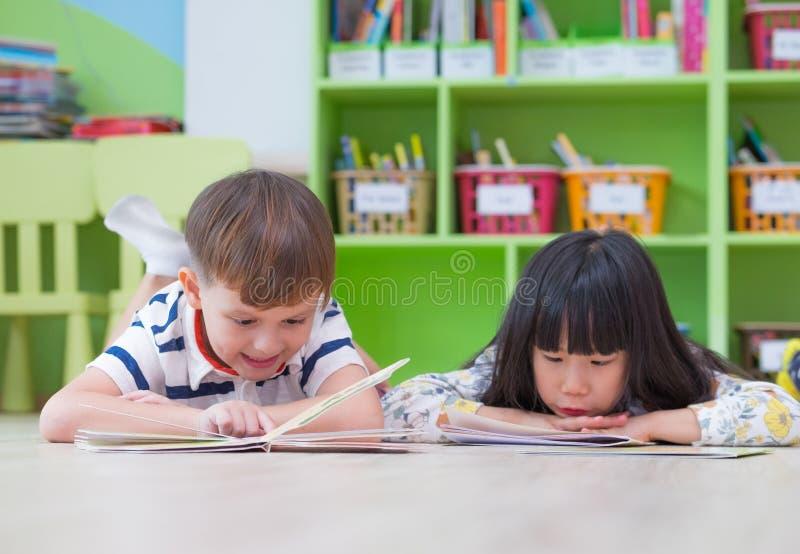 两孩子放下在地板和读书传说书在学龄前图书馆,幼儿园学校教育概念里 免版税库存照片