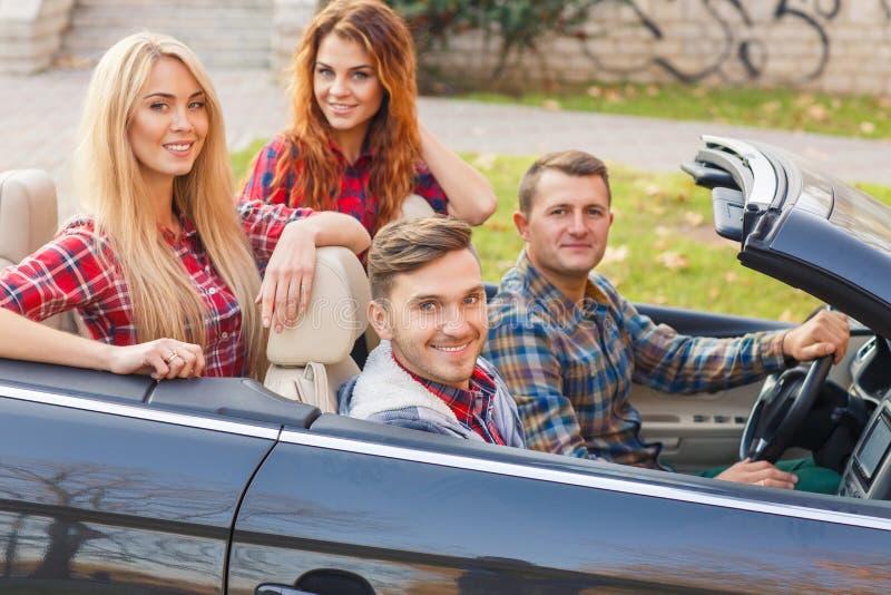 两对在一辆黑敞篷车的年轻夫妇乘驾 库存照片