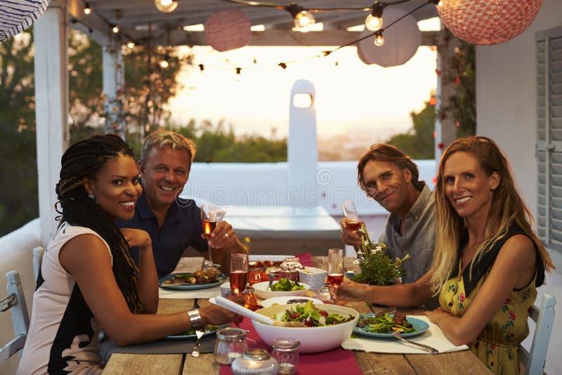 两对夫妇吃在屋顶大阳台神色的晚餐对照相机 免版税库存图片