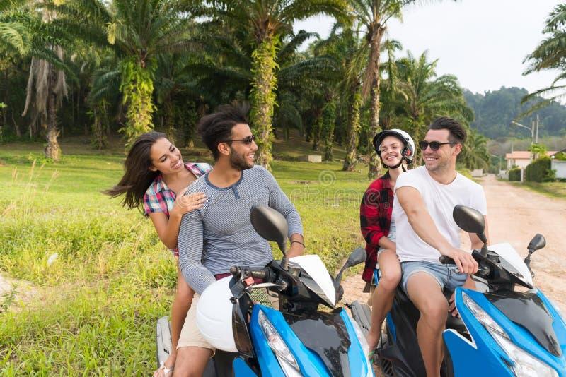 两对夫妇骑马摩托车、年轻人和妇女旅行在自行车在热带森林公路 免版税库存图片