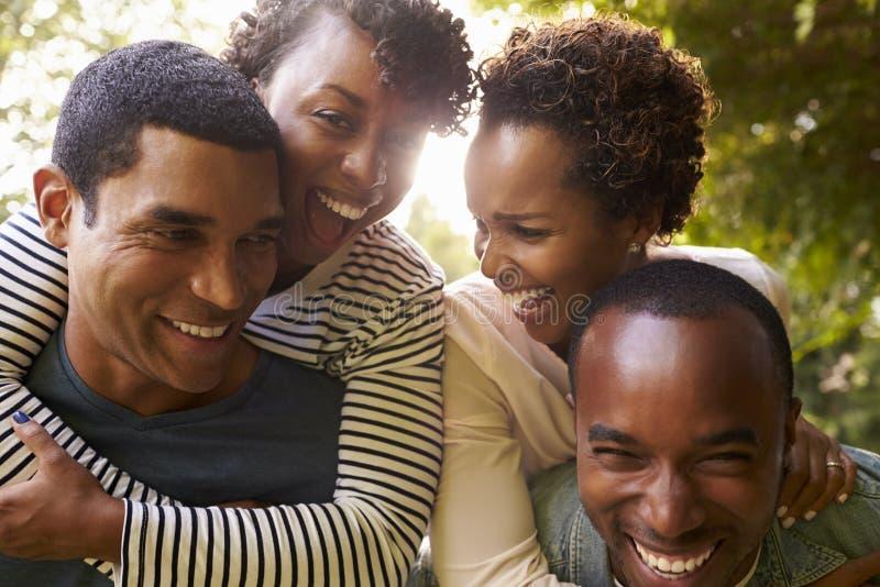 两对成人黑夫妇获得扛在肩上的乐趣,接近  库存照片