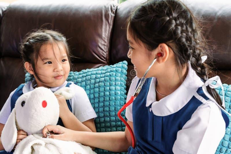 两小女孩是微笑和扮演有听诊器的医生 孩子和医疗保健概念 库存图片