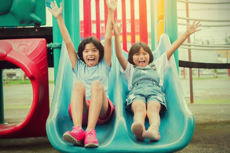 两小女孩获得演奏滑子的乐趣在同水准的操场 库存图片
