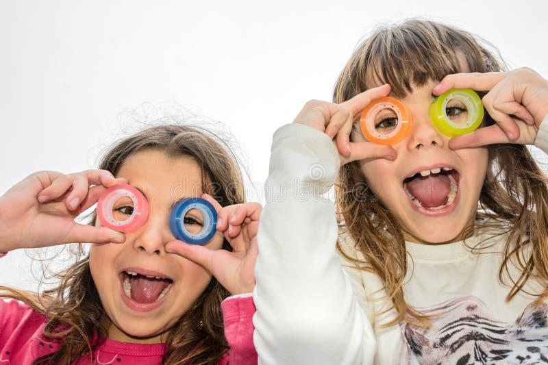两小女孩通过一卷透明胶带的圈子看 免版税库存图片