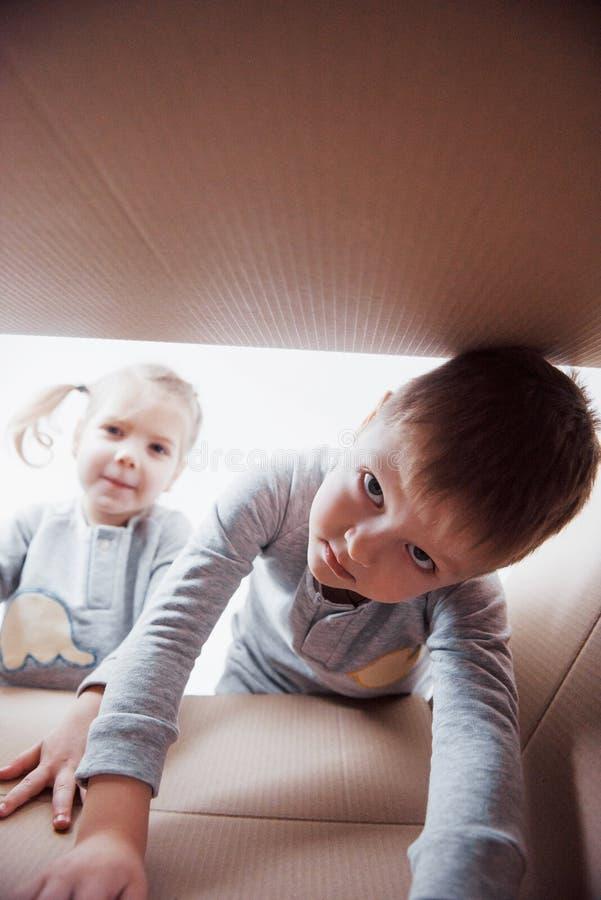 两小孩打开纸板箱和上升在它中间的男孩和女孩 儿童乐趣有 免版税库存图片