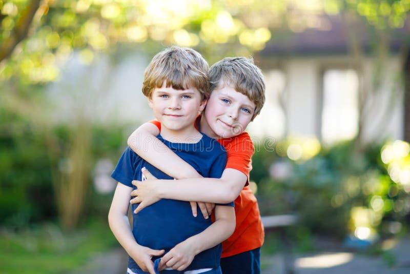 两小的活跃学校哄骗拥抱在夏日的男孩、孪生和兄弟姐妹 免版税库存图片