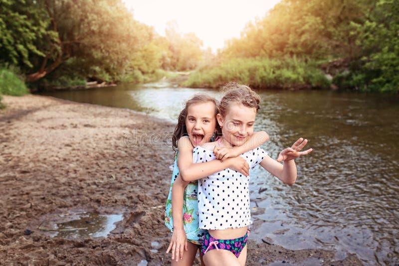 两少女获得在河的乐趣 免版税库存图片